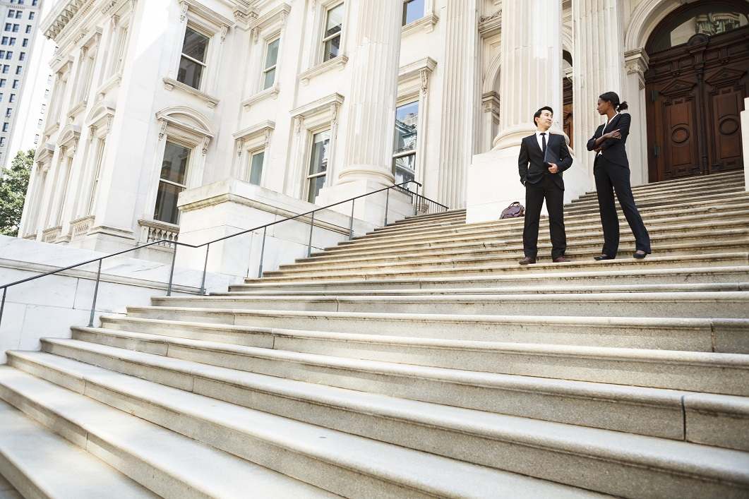 Legal professionals converse on steps of municipal building